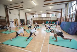People in yoga poses on mats in a sports hall