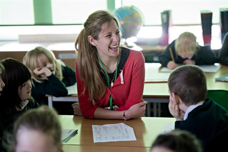 female trainee teacher in school setting smiling with pupils