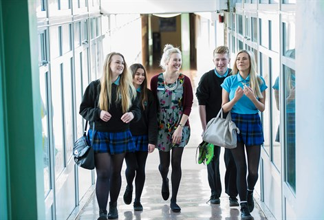 Female teacher walking down corridor with pupils