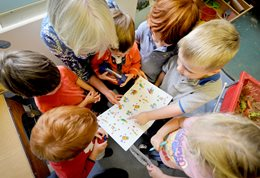 Nursery children pointing things out on a sheet of paper