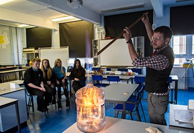 Controlled chemical fire experiment at the front of a secondary school chemistry classroom