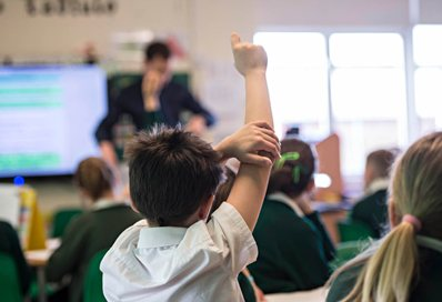 A primary school pupil with his hand in the air in front of his teacher