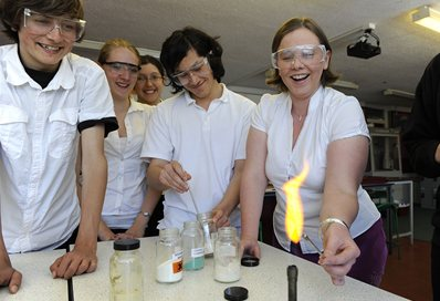 Students in a classroom testing chemicals in the flame of a bunsen burner