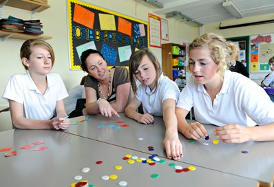 Pupils in a classroom working out sums with plastic counters