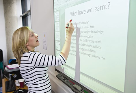 education student works on interactive whiteboard