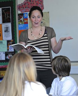 Student teacher reading from a book to pupils