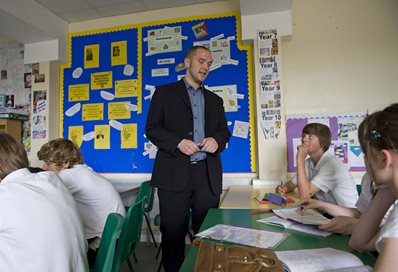 Suited member of staff talking to a class of secondary religious education students