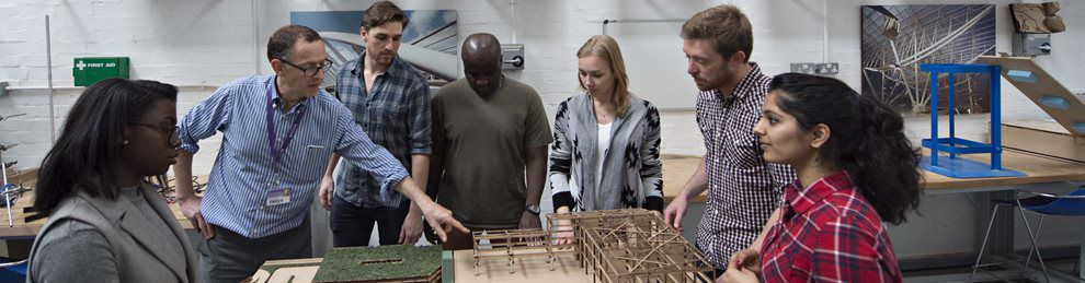 Students and a lecturer having a discussion over an architectural model
