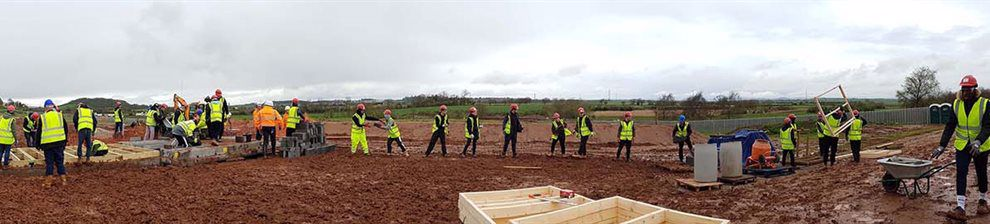A line of construction students handing items across a muddy field