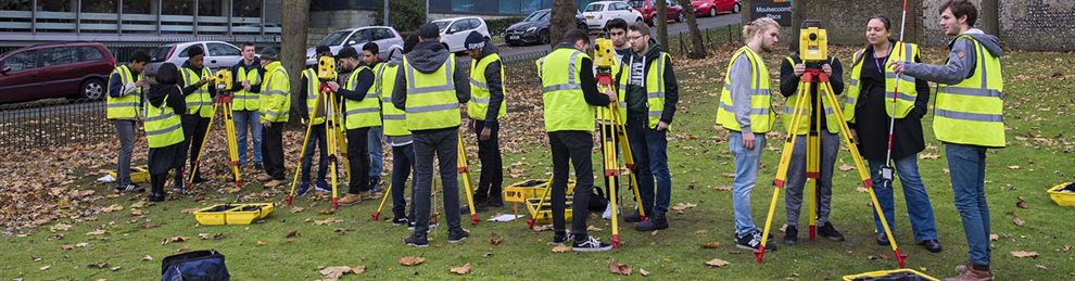 Construction students using equipment to survey a field