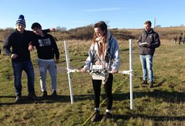 Students in a field with some earth analysing equipment