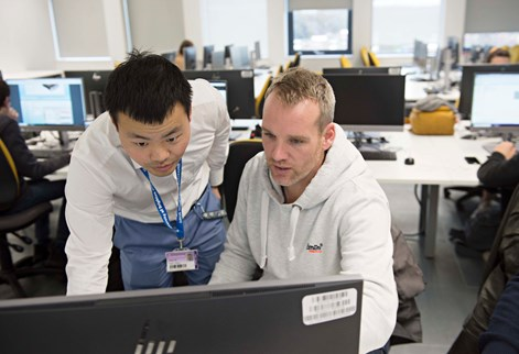 Student and lecturer studying computer diagrams