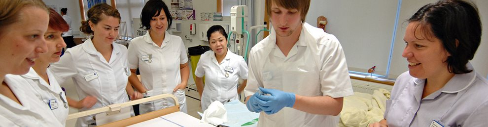 Nursing students round a bed in our clinical skills facility