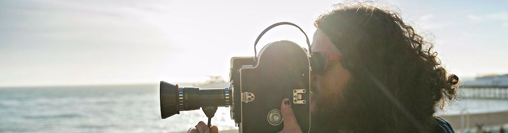 Close up of a student holding a film camera on the beach, pointed at the sea