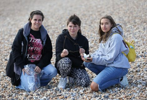 Students on beach holding rubbish in their hands