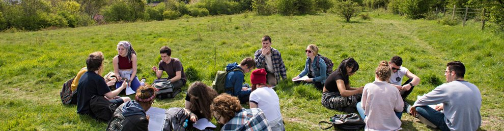 Students sitting in a woodland clearing on an ecology field trip