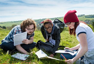 Ecology students on a field trip taking grass samples