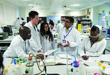 Pharmacy lecturer and students working in the labs