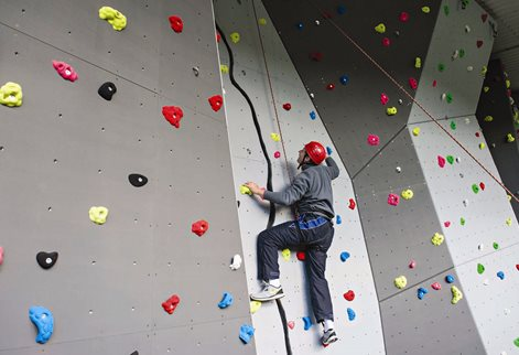 A student scaling the climbing wall
