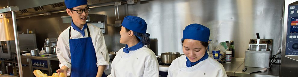 Three hospitality students wearing aprons and hats in a kitchen location