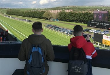 Two students looing over a horse racing course