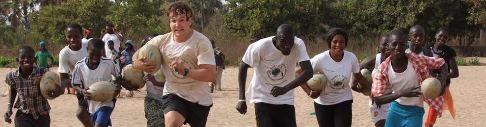 An MA student teaching local villagers how to run with a rugby ball in an African village.