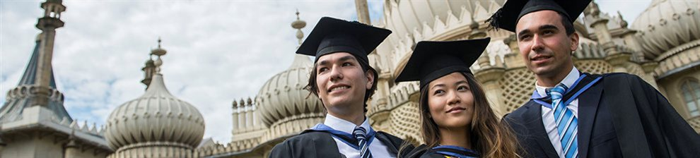 Three graduates in mortar boards and gowns in front of the Royal Pavilion