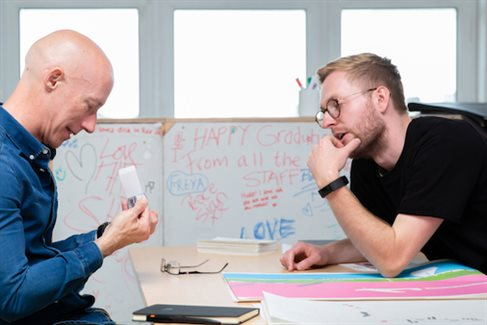 male student and male lecturer discuss portfolio at interview