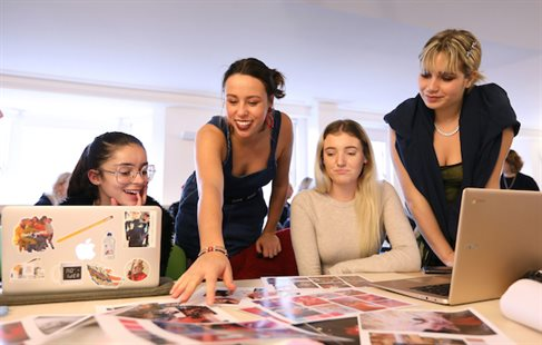 female lecturer with three female students review photos on table