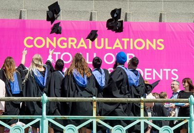A group of graduates on the seafront promenade throwing their mortar boards in the air