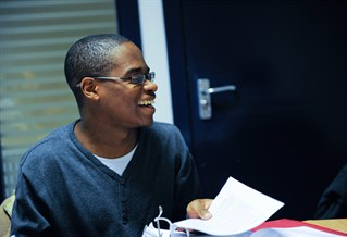 A student holding a folder and laughing