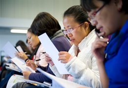 Students reading notes in a seminar