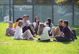 Students sitting in a ring on the grass