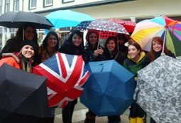 A group of students in the rain with many different umbrellas open