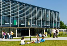 Students sitting on the grass outside Checkland building at Falmer campus