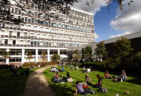 People sitting on the grass in front of the Cockcroft Building