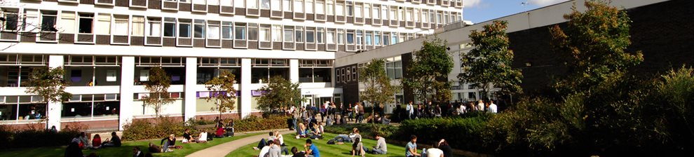 Students sitting on the grass outside the Cockcroft Building