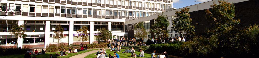 Students sitting on grass outside the Cockcroft building