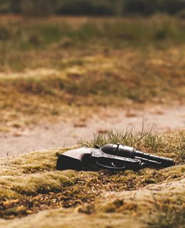 Revolver in the sand Photo by Jens Lelie on Unsplash