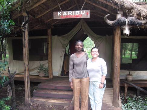 Two women standing outside a small wooden building, with a sign: KARIBU basecamp
