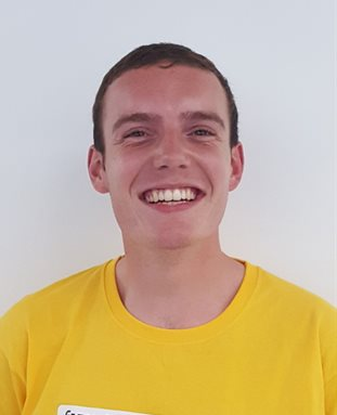 A smiling James Lewington in a bright yellow t-shirt